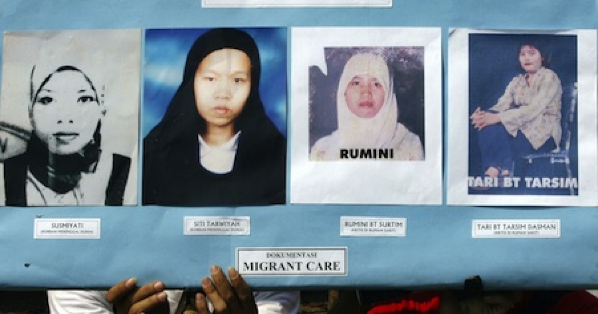 Activists shows a placard displaying photos of abused Indonesian women migrant workers during a 2007 demonstration in front of Saudi Arabian embassy in Jakarta.</p>