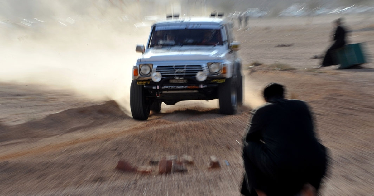 A Saudi man looks at a car competing during the first day of the International Hael Desert Challenge 2011, a desert rally race, in Hael, some 600 kms northern Riyadh.</p>