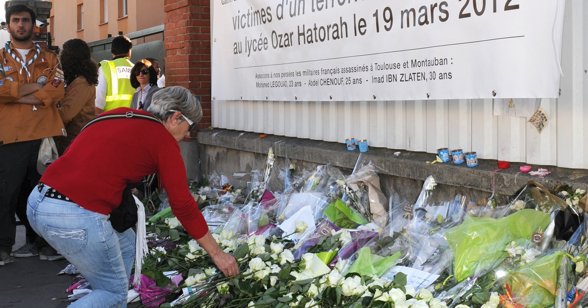At the end of a march by people from all faiths on Sunday, a woman lays a white rose in front of the Ozar Hatorah Jewish school in the southwestern city of Toulouse, where three children and one teacher were killed last week by self-proclaimed Islamist Mohamed Merah.</p>