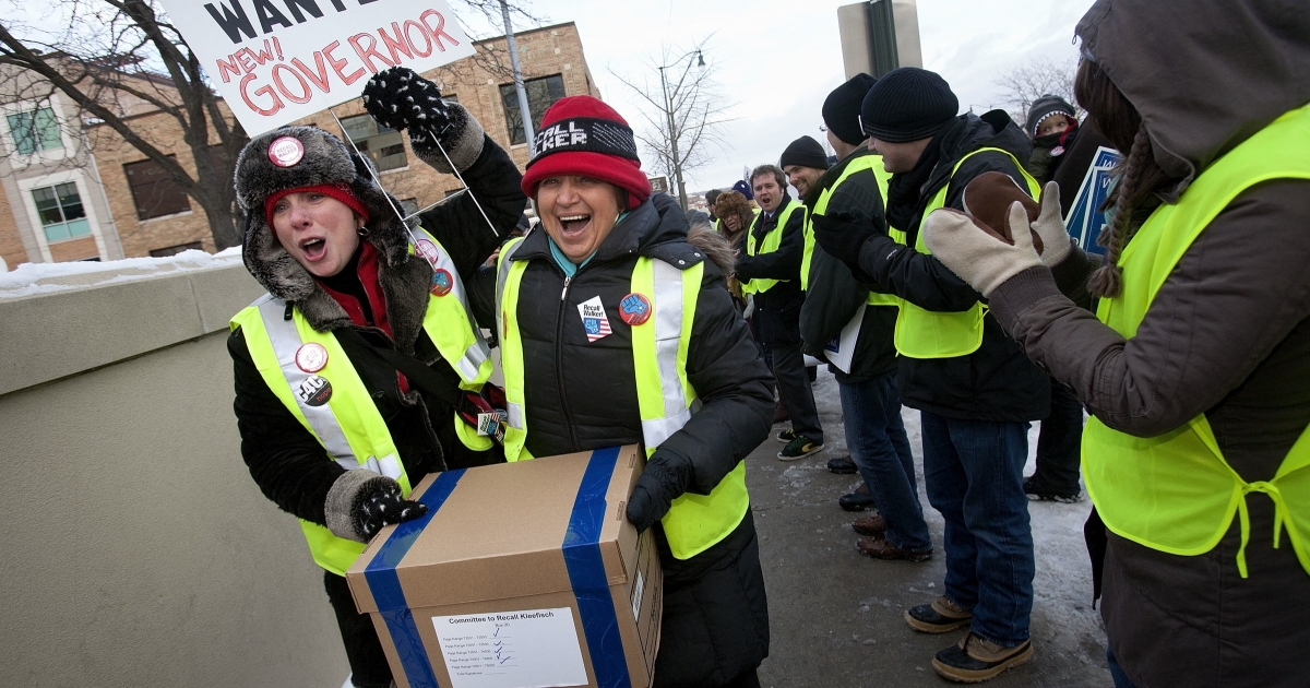 Spectators cheer and applaud as recall volunteers walk through a gauntlet of supporters on their way to deliver boxes containing signatures to recall Gov. Scott Walker to the Government Accountability Offices in Madison, Wisc., on Jan. 17, 2012.</p>