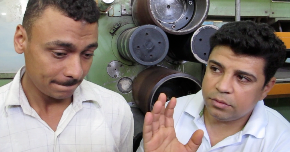 Two employees of the Shebin al-Kom Textile Factory talk about the plant, which is currently at a standstill while the Egyptian government takes control of operations, in October 2011.</p>