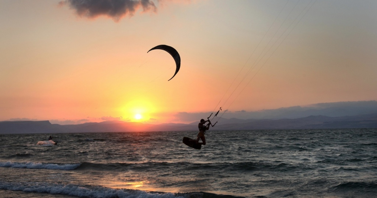 An Israeli man practices kite surfing during sunset in the Sea of Galilee in northern Israel on September 5, 2009.</p>
