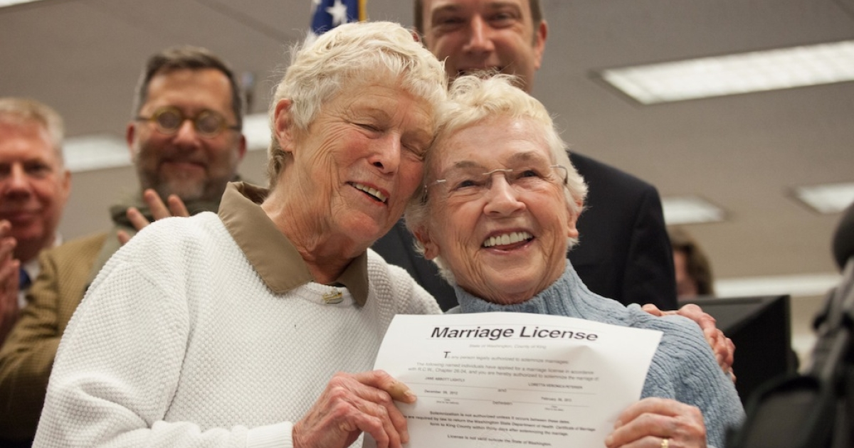 SEATTLE, WA - DECEMBER 6: Jane Abbott Lighty, left, and Pete-e Petersen embrace after receiving the first same-sex marriage license in Washington state at the King County Recorder's Office on December 6, 2012 in Seattle, Washington. The office opened at 12:01 a.m. to begin issuing marriage licenses to same-sex couples for the first time after Washington voters chose to legalize gay marriage in November's election. (Photo by David Ryder/Getty Images)</p>