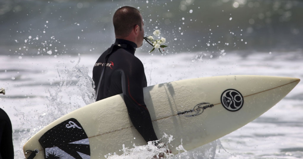 Surfers wade into the ocean for