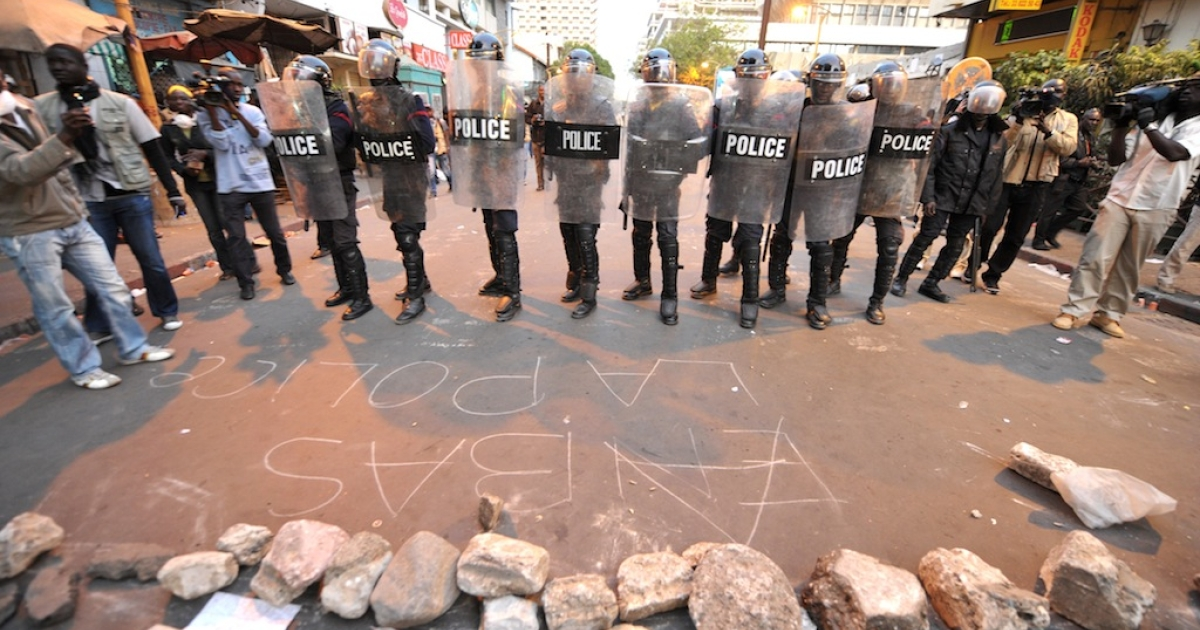 Text written on the ground in chalk reads 'Down with the police' as riot policemen stand guard, blocking access to Independence Square during an opposition demonstration against Senegal's President Abdoulaye Wade's controversial bid for a third term, on Feb. 23, 2012, in Dakar.</p>