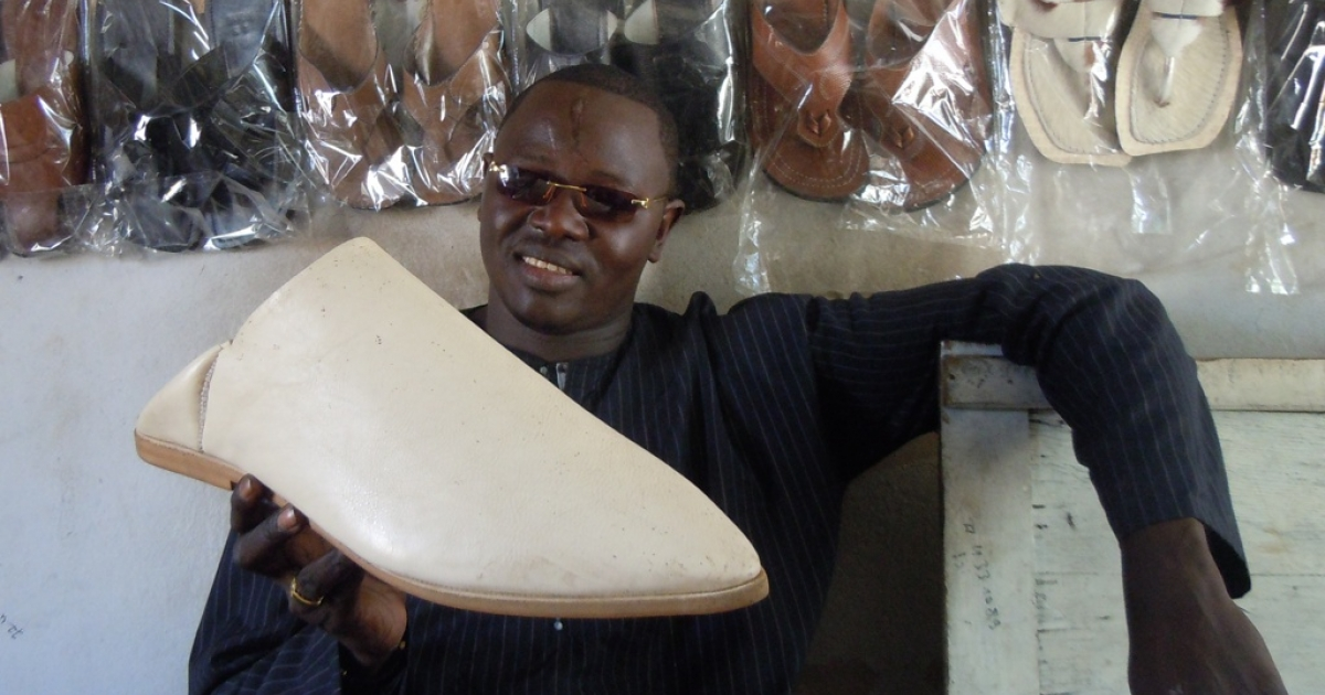 Momodou Thiam, head of a shoe workshop in Ngaye Mekhe, holds up this oversized babouche that he is, perhaps, as likely to sell as any of his over-stocked shoes.</p>