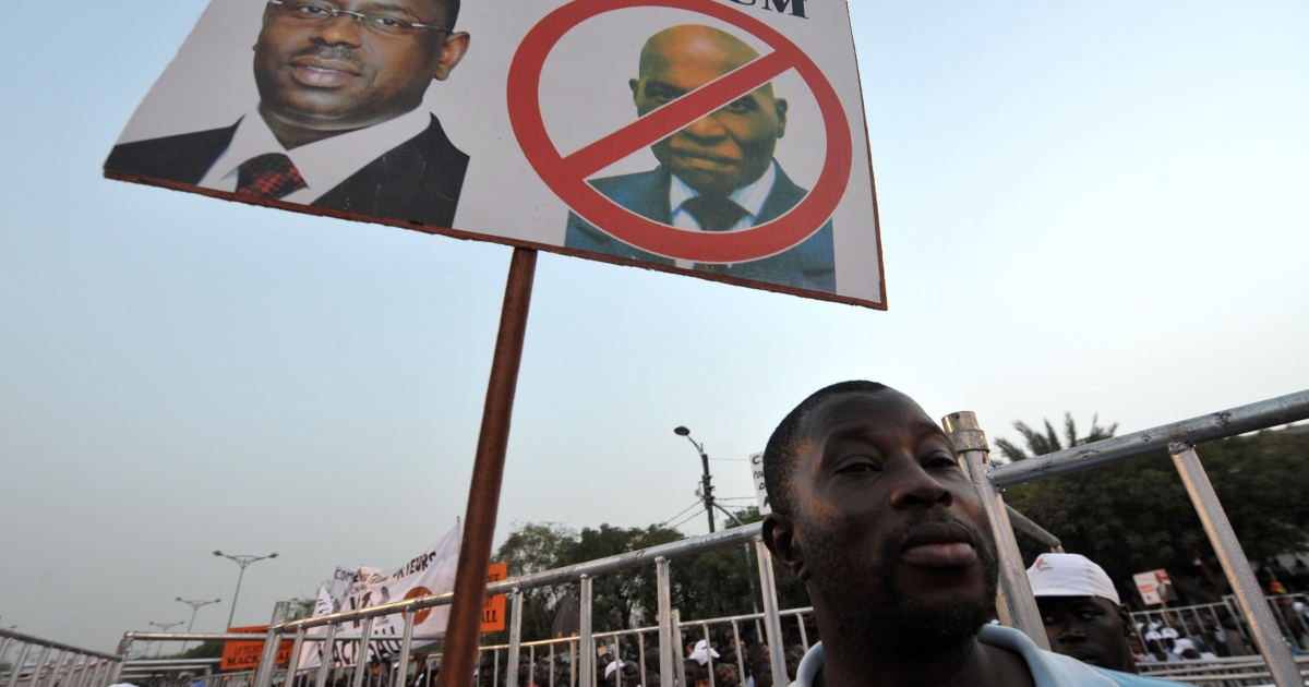 A supporter of Senegalese opposition candidate Macky Sall holds a placard depicting a portrait of his candidate (L) and a barred one of incumbent President Abdoulaye Wade on March 12, 2012 in Dakar. Senegal's opposition joined forces today in a mass rally to block 85-year-old President Abdoulaye Wade from landing a third term in office.</p>