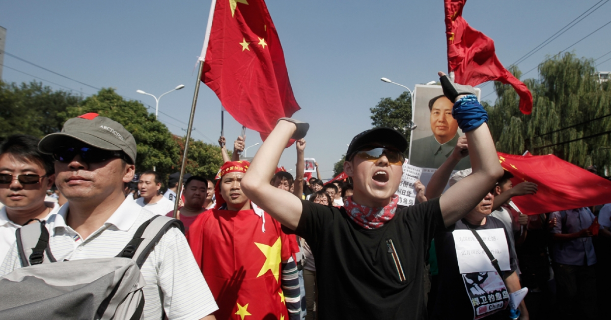 Demonstrators hold flags and a portrait of Chairman Mao during an anti-Japanese protest over the Diaoyu Islands issue outside the Japanese Embassy on Sept. 15, 2012, in Beijing, China. Tensions in the area continue to simmer despite reports that China plans to remain 'non-confrontational' in its foreign policy dealings.</p>