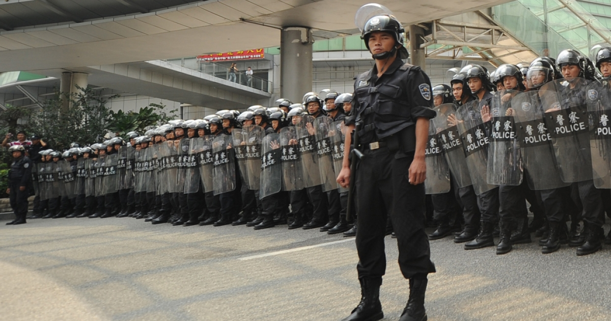 Riot police stand guard as anti-Japan protesters march during a protest over the Diaoyu islands issue, known as the Senkaku islands in Japan, in the southern Chinese city of Shenzhen on September 18, 2012. Thousands of anti-Japan protesters rallied across China over a territorial row on a key historical anniversary, as Japanese firms including car giant Toyota shut or scaled back production in across the country.</p>