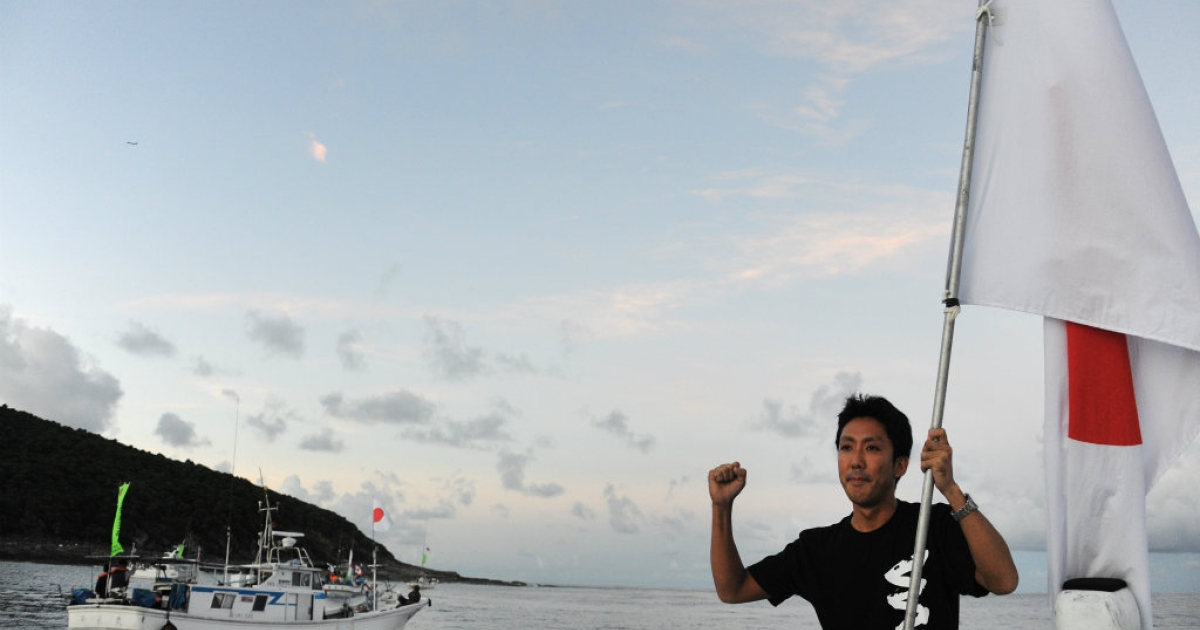 An activist holds the Japanese flag before a group placed the country's flag on a disputed island, part of a group known as Senkaku in Japanese and Diaoyu in Chinese.</p>