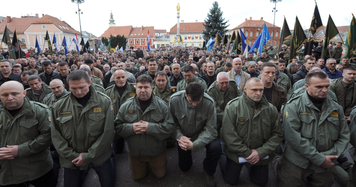 Croatian war veterans from the 1991-1995 Serbo - Croatian war kneel down as they pray in front of main Zagreb's cathedral in December, 2009. A special Serbian war crimes court sentenced 14 ex-soldiers and paramilitaries to 128 years in prison for the killings of 70 Croat civilians in 1991 on June 26, 2012.</p>