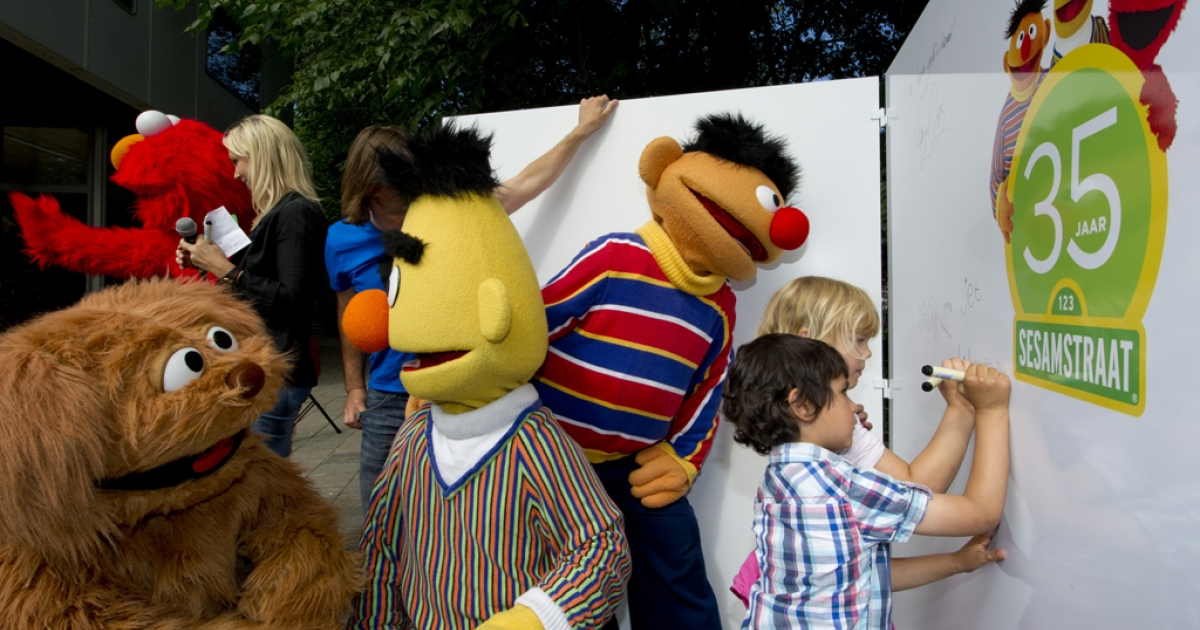 Children sign a wall as they mark the 35th anniversary of Sesame Street flanked by characters Elmo, Tommie, Bert and Ernie at the Dalton School in Amsterdam, on July 20, 2011.</p>
