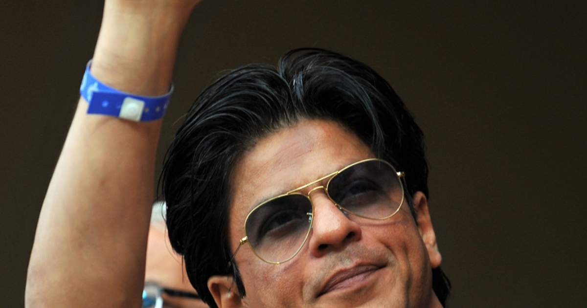 Bollywood actor Shah Rukh Khan waves to the crowd during a cricket match between Royal Challengers Bangalore and Kolkata Knight Riders in Bangalore on April 10, 2012.</p>