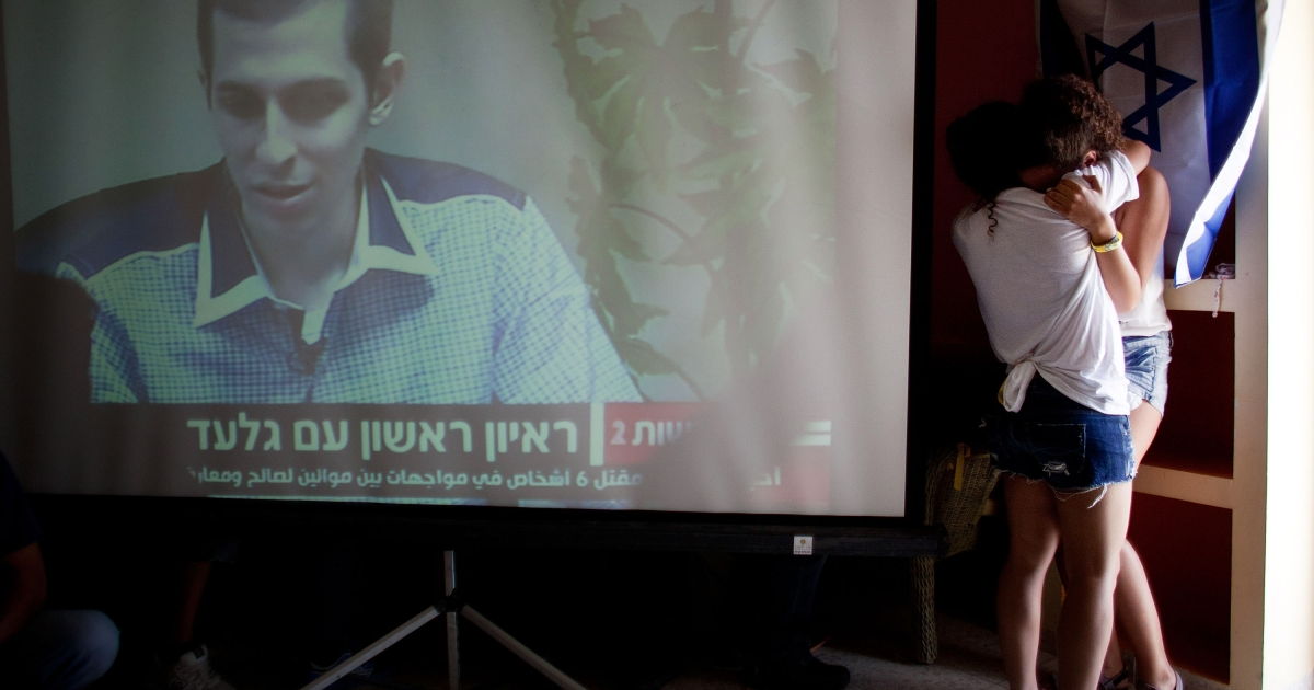 Israelis react after seeing the first images of Israeli Defense Forces soldier Gilad Shalit on TV following his release on October 18, 2011 in Mitzpe Hila, Israel.</p>