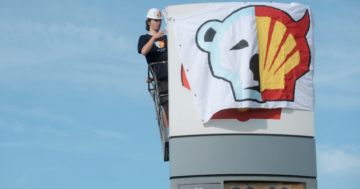A Greenpeace environmental activist covers the logo of the Shell oil company to protest on May 10, 2012 against the heading of the an icebreaker for Shell's Arctic oil drilling project in the north of Alaska.</p>