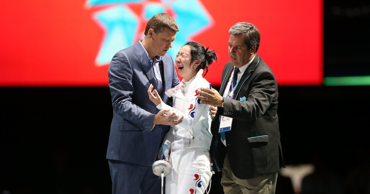 Shin A-Lam of Korea gets escorted off stage after a faulty clock ended her match against Britta Heidemann of Germany in the Women's Epee Individual Fencing Semifinals on Day 3 of the London 2012 Olympic Games.</p>