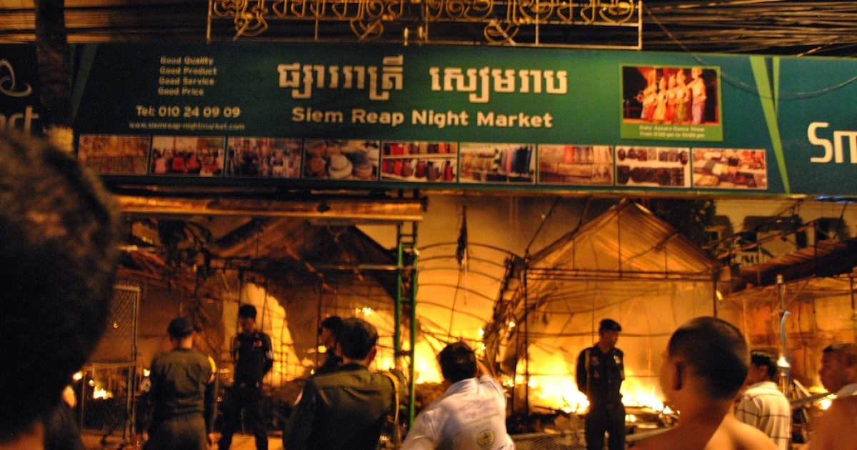 Cambodian officers stand guard as a night market (back) burns in Siem Reap province, some 300 kilometers northwest of Phnom Penh in the early hours on December 8, 2012. Eight people, including four children, were killed in a fire that tore through a popular night market in the Cambodian tourist town of Siem Reap early December 8, police said.</p>