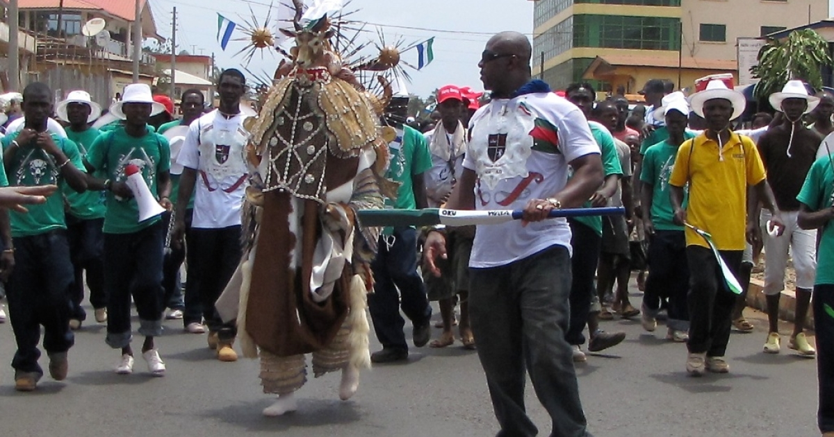 An impromptu parade formed on Wilkinson Road, the main road through the western area of Freetown. Here a man in a traditional celebratory costume is among the marchers.</p>