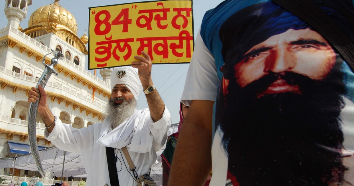 An activist from a radical Sikh prganisation wears a shirt depicting Sikh leader Sant Jarnail Singh Bhindranwale (R) whilst another holds a placard and a sword after prayers at Sri Akal Takht at the Golden Temple in Amritsar on June 6, 2011. 'Ghallughara Diwas' is the anniversary of the deadly 1984 Indian army 'Operation Bluestar' assault on the Golden Temple complex to arrest Sant Jarnail Singh Bhindranwale, a Sikh leader and his militant followers who had initiated a movement for a separate Sikh state.</p>