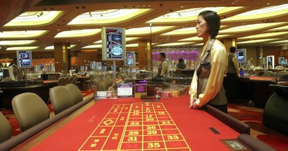 A croupier stands next to a gaming table during the opening of the Marina Bay Sands casino in Singapore on April 27, 2010. Singapore threw open the doors of its second casino Tuesday, giving a fresh boost to the city's tourism sector and raising its profile as a playground for the world's high-rollers.</p>