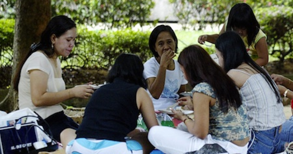 Domestic helpers enjoy a picnic in the shade at 'Gulung-gulung' park in Singapore.</p>