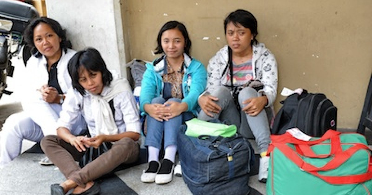 Newly arrived domestic helpers from Indonesia wait for their transportation to a maid agency after going through medical check in Singapore on March 6, 2012.</p>