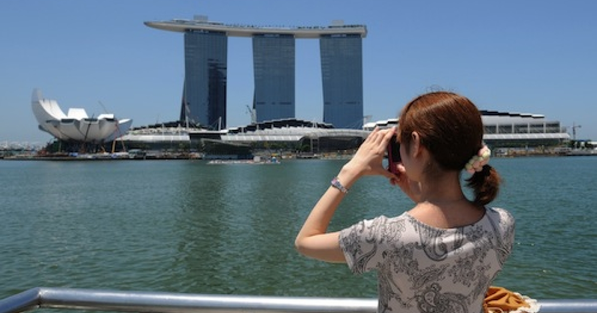 A woman in Singapore viewing a casino, the Marina Bay Sands.</p>