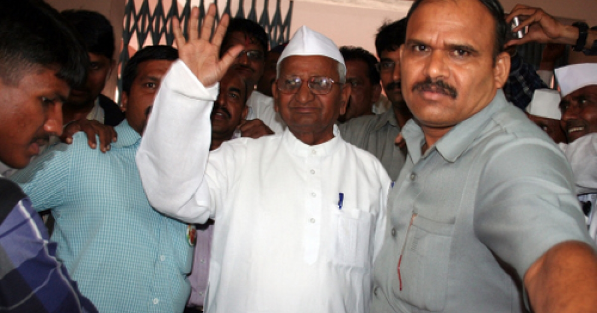 Anna Hazare (C), the Indian anti-corruption activist whose 13-day fast forced the government to reconsider a new law tackling graft, waves to supporters in his village of Ralegan Siddhi on September 2, 2011.</p>
