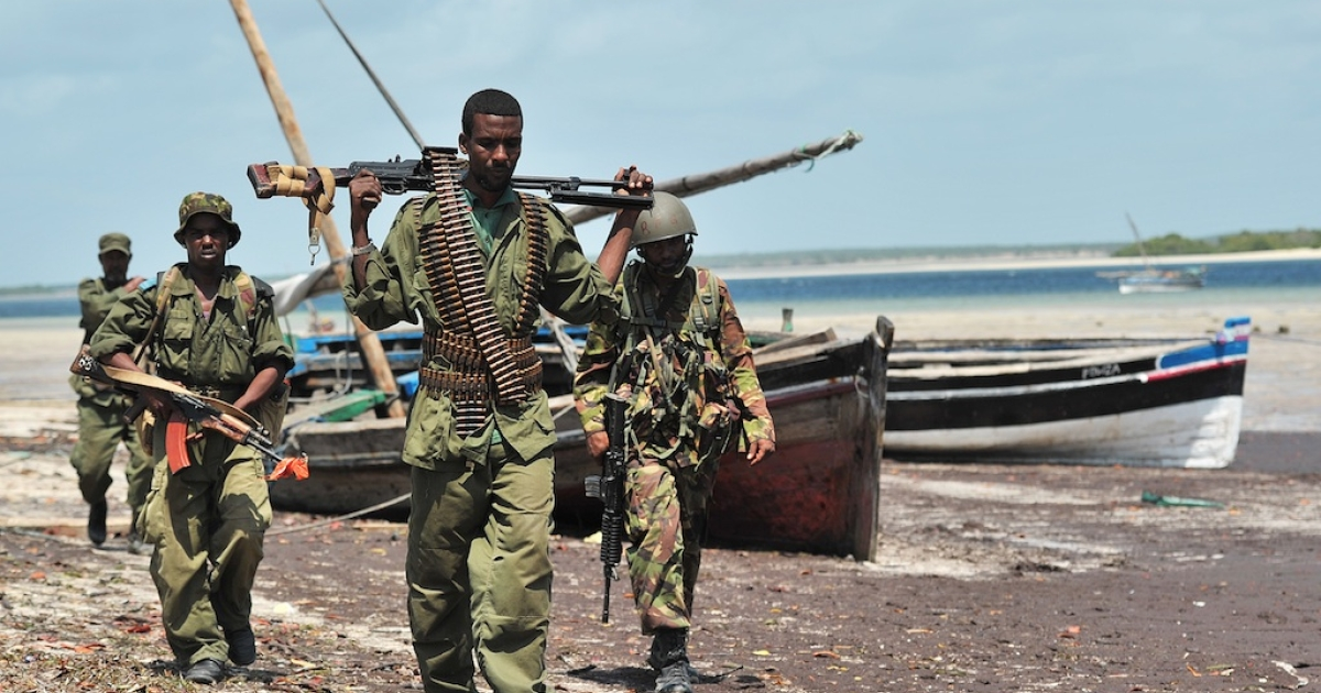 Militia allied with the Federal Government of Somalia and Kenyan Defence Force soldiers walk along the coast near Burgabo village, Southern Somalia on December 14, 2011. Burgabo is a Somalian port village which has been secured by Kenyan forces as they advance further up the Somali coastline in search of Al-Shabaab fighters.</p>