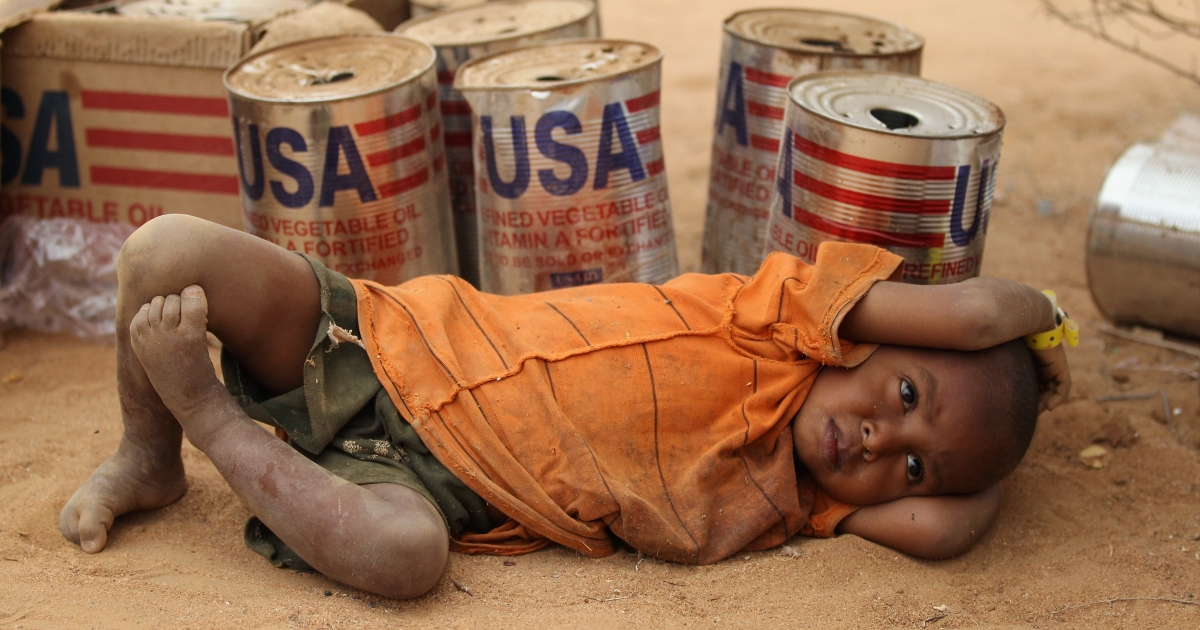 A young Somali refugee rests by empty vegetable oil tins delivered by USAID to the Dadaab refugee camp in Kenya. The boy is seen on July 20, 2011 at the Dagahaley refugee settlement inside Dadaab.</p>