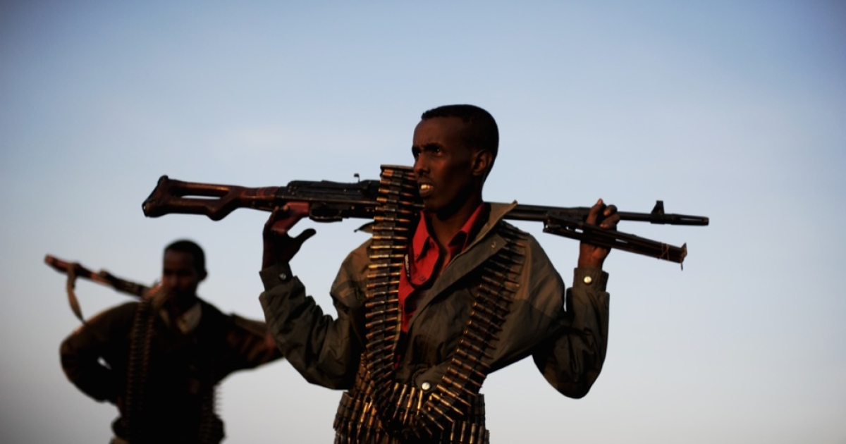 Men providing security for a local official hold their weapons as they stand in a field in the plains near the central Somali town of Galkayo on Aug. 18, 2010.</p>