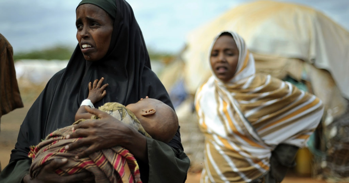 A displaced Somali refugee cradles her severely emaciated child at the Dadaab Refugee camp, in eastern Kenya, where around 1,500 people are arriving every day in search of food, water and medical care.</p>