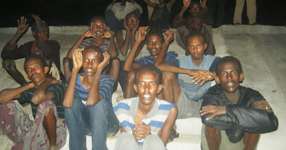 Somali pirates get their own movie. Here, suspected Somali pirates that arrived on the coast of Dwarka by boat sit on the ground as they are guarded by marine reserve police in Jamnagar district in Gujarat state on June 26, 2011. Indian police detained 18 suspected Somali pirates.</p>