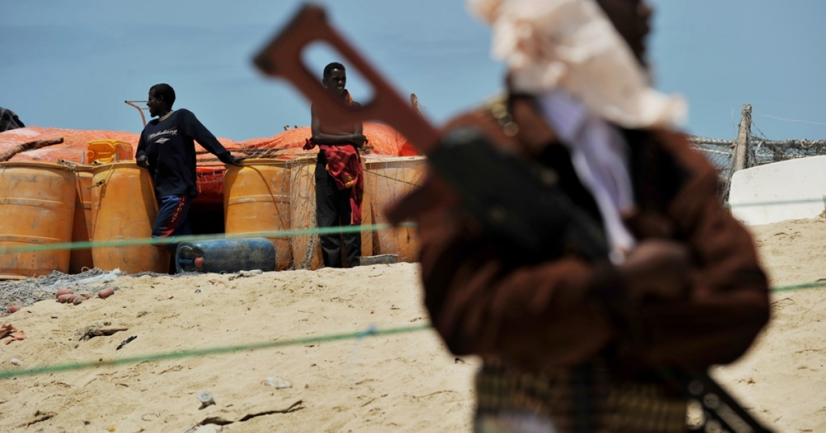 A pirate folds his arms over his high-caliber weapon near two boys standing next to plastic drums filled with gasoline on a beach in the central Somali town of Hobyo on August 20, 2010.</p>