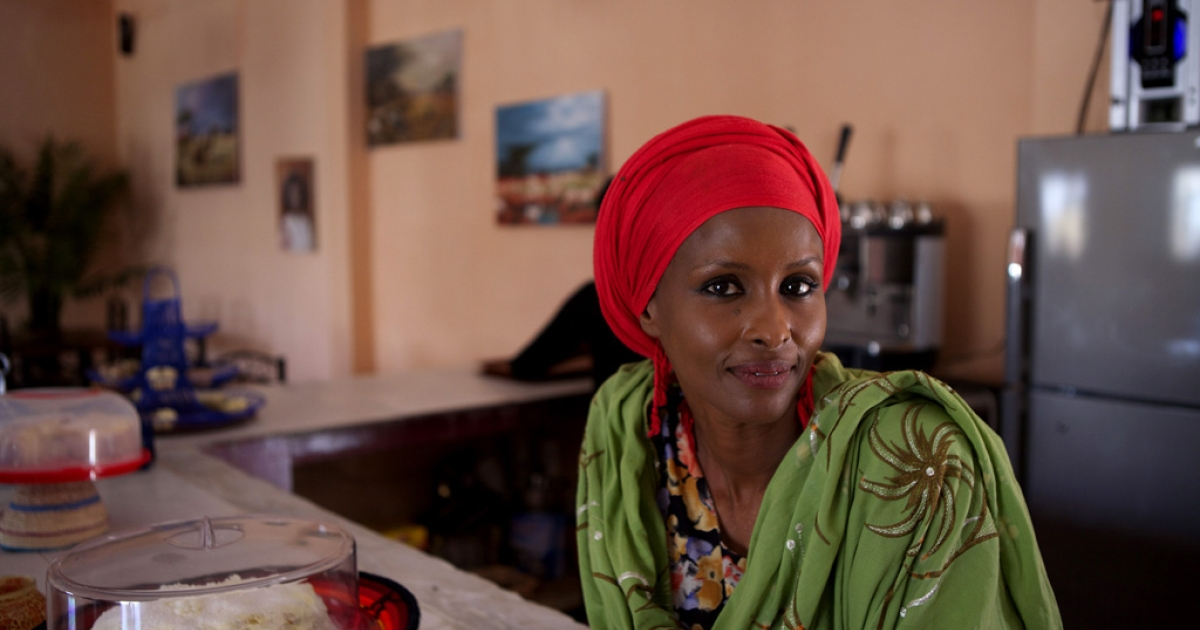 British-Somali woman Ayan Hussein stands behind the counter at her newly opened Kulan Art Cafe in Hargeisa.</p>