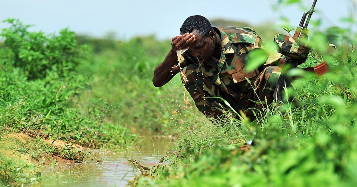 A Somali militia washes his face in a lush field near an irrigation scheme that grows onions and vegetables near Doloow, central Somalia, on Nov. 21, 2011.</p>