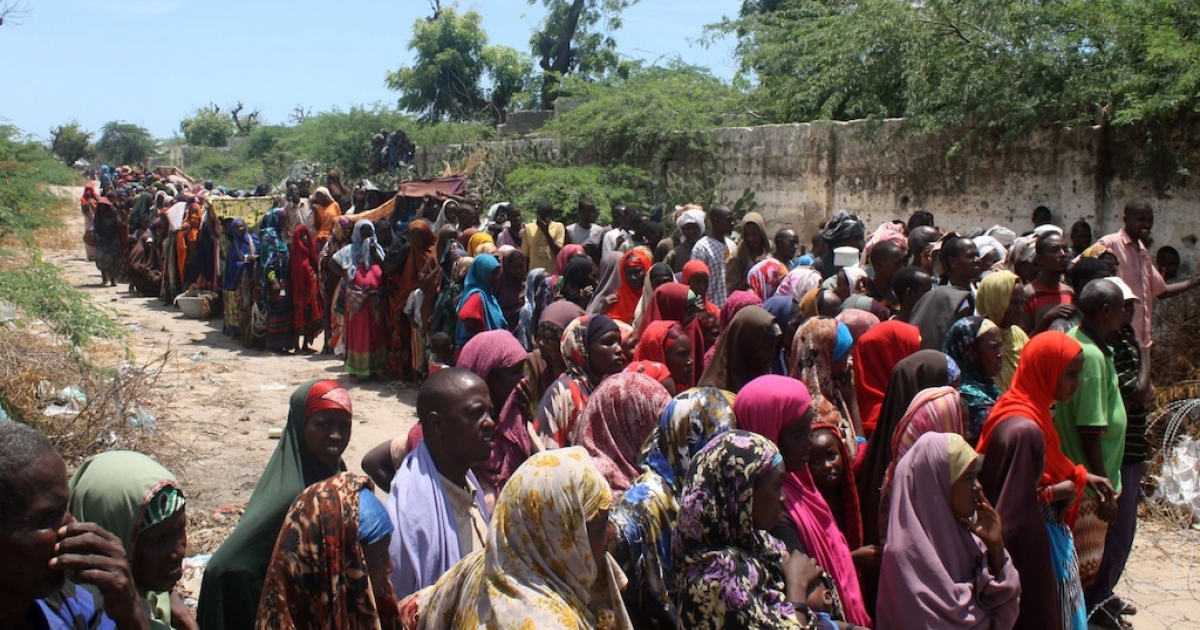 Families from southern Somalia line up for aid from aid agency at Howl Wadaag district in Mogadishu on Oct. 15, 2011.</p>