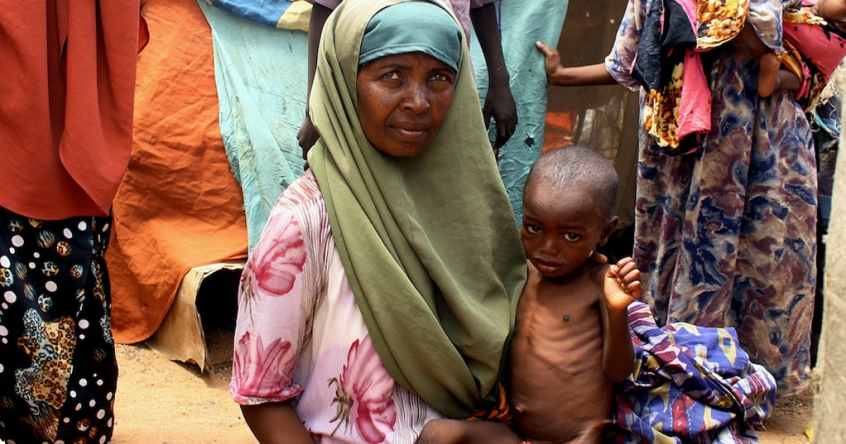 Kadijo Suleyman, an internally displaced person from southern Somalia, holds her malnourished child in front of her makeshift shelter on Aug. 25, 2011, at the Taraboonka IDP camp in Mogadishu.</p>