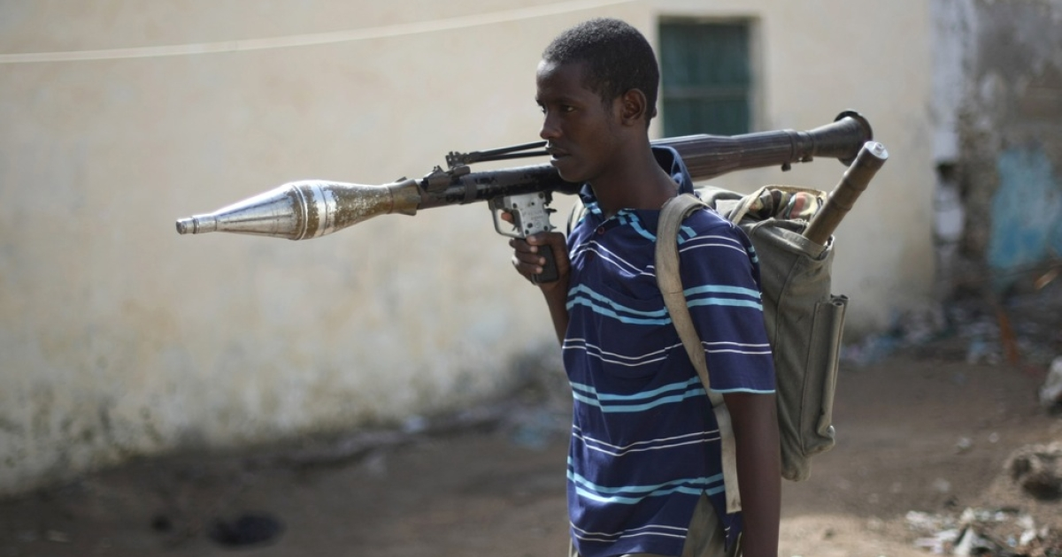 An Al-Shabab Islamic fighter, wearing a rock launcher, walk at a front line section in sanca district in Mogadishu.</p>