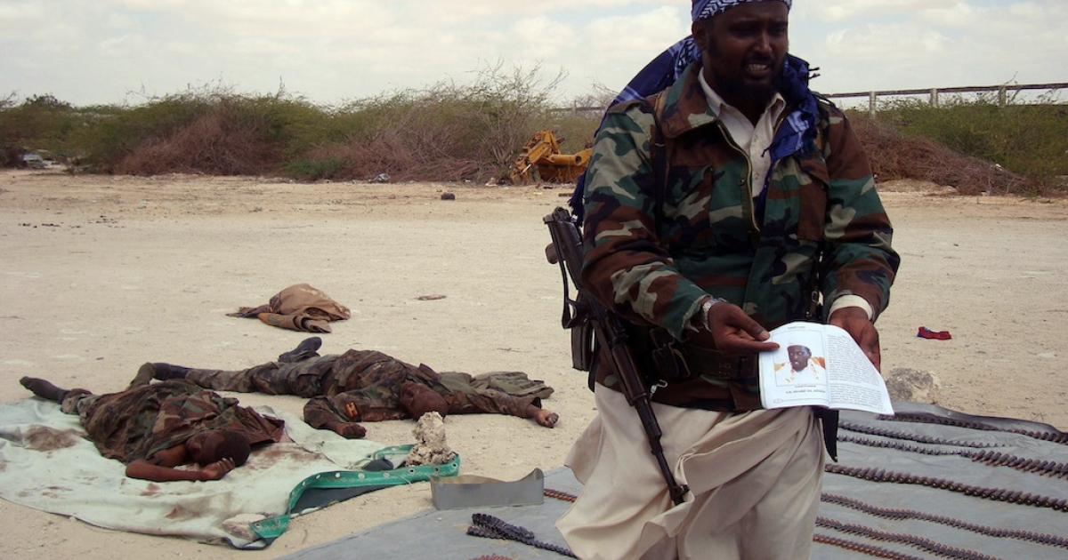 An ex-US soldier tried to join Somalia's Al Shabaab militants. Here, a spokesman of the Al Qaeda-linked militants in Somalia, Sheik Ali Mohamud Rage holds a picture of Somalia President Sharif Sheik Ahmed during a display of the bodies of two alleged Ugandan soldiers they claimed to have killed during clashes in Mogadishu on February 20, 2011. The African Union mission in Somalia (AMISOM) said the fighting was triggered by its discovery of a mile-long trench system used by the Al Qaeda-inspired Al Shabaab insurgents in the capital.</p>