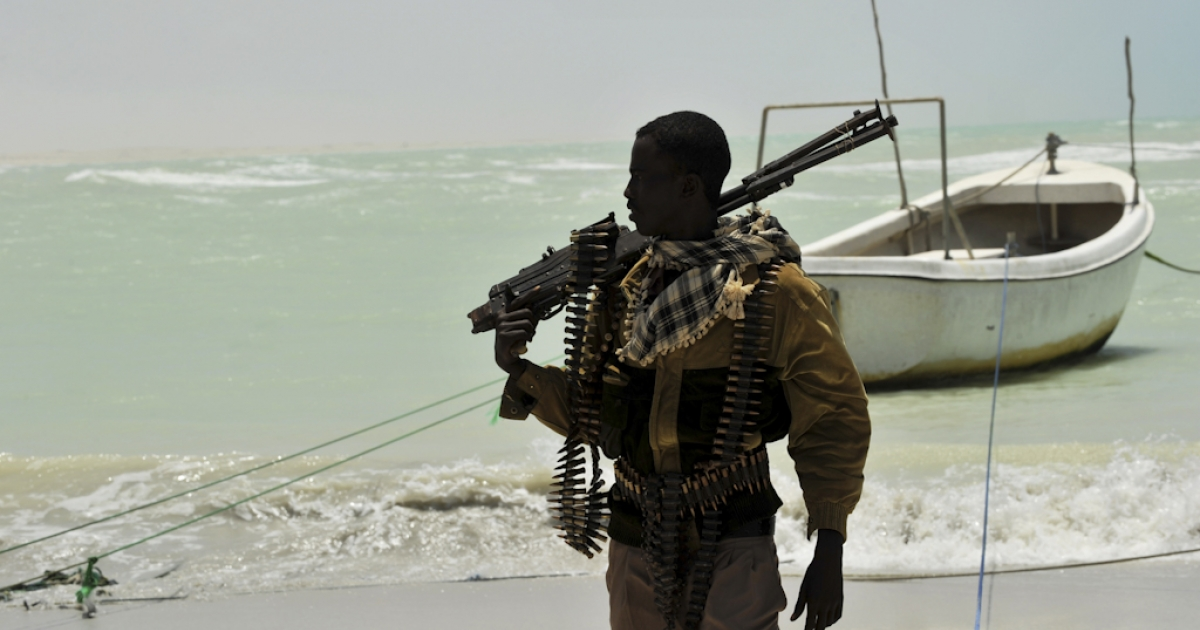 A Somali man, part armed militia, part pirate, carries his high-caliber weapon on a beach in the central Somali town of Hobyo.</p>