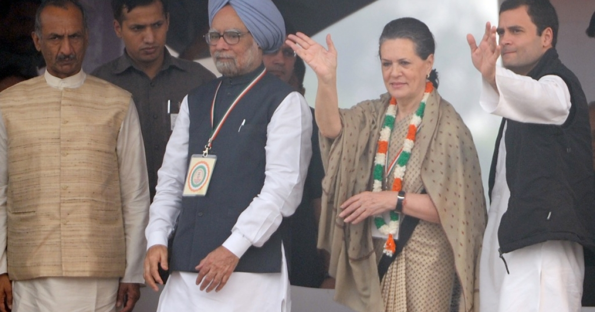 Indian Prime Minister Manmohan Singh (2L) and Congress Party General Secretary Rahul Gandhi (R) join Congress President and UPA Chairperson Sonia Gandhi (C) as she waves towards supporters during a party rally at The Ram Lila Grounds in New Delhi on November 4, 2012.</p>