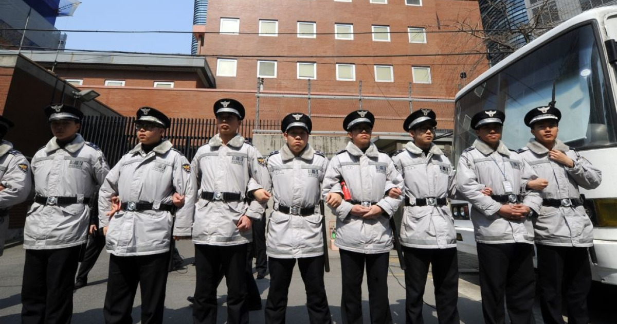 Policemen stand guard in front of the Japanese embassy as South Korean protesters hold a rally against new Japanese textbooks in Seoul on March 30, 2011.</p>