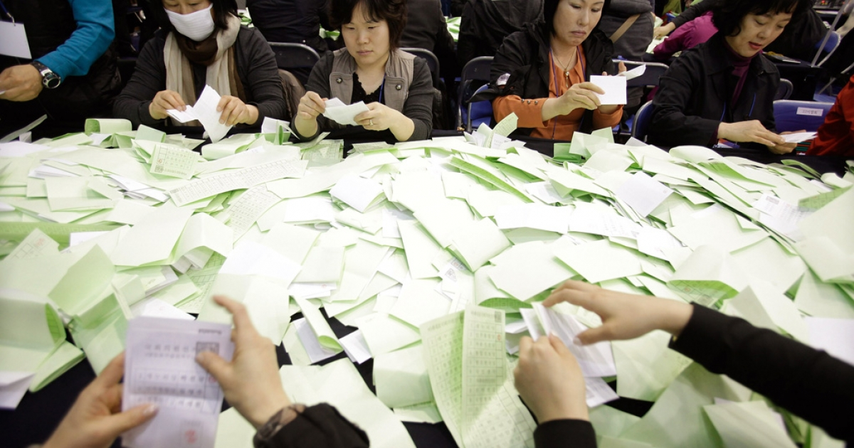Officials from the South Korean Central Election Management Committee count votes at the Yuido High School on April 11, 2012 in Seoul.</p>