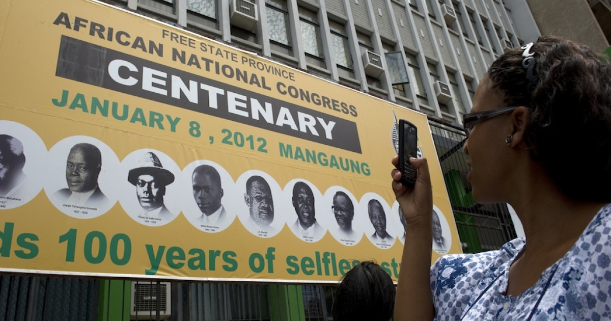 A woman takes a picture of a poster in Bloemfontein on January 5, 2012 to celebrate the 100th anniversary of South Africa's ruling African National Congress (ANC) party.</p>