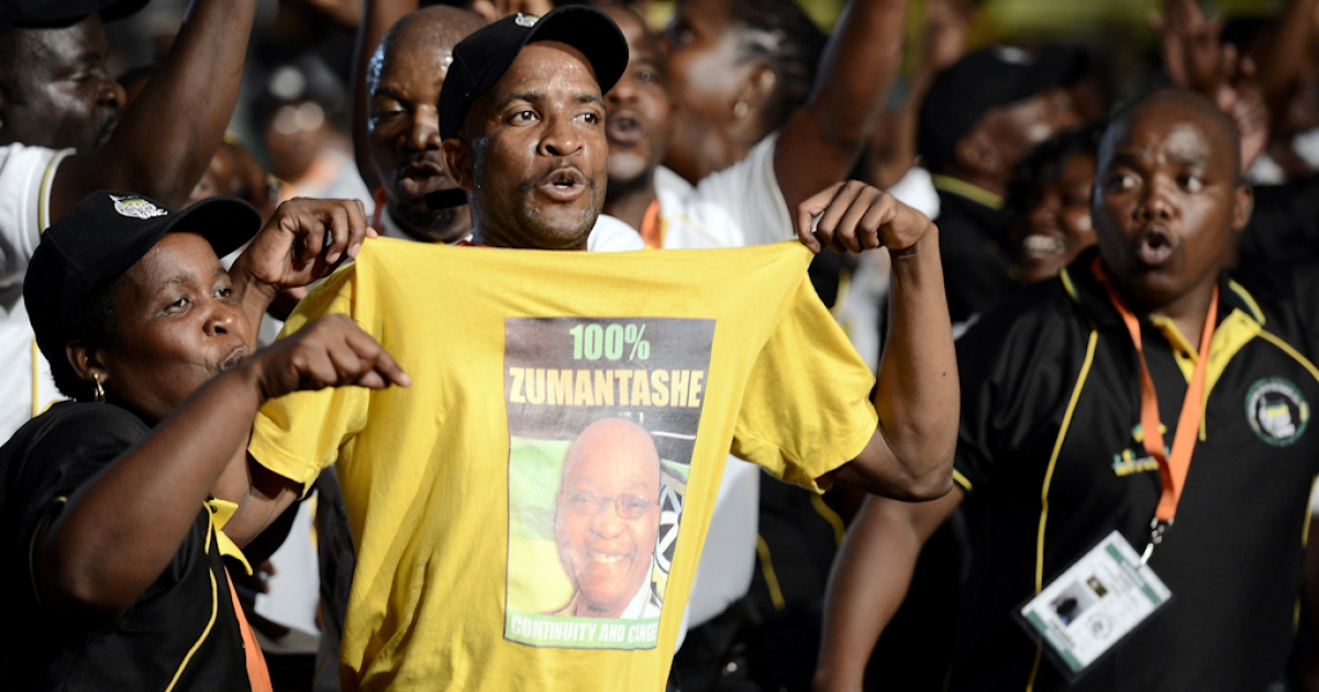 A supporter of South African President Jacob Zuma holds a t-shirt baring his portrait, among African National Congress (ANC) delegates attending the opening ceremony of the 53rd National Conference of the African National Congress (ANC) on December 16, 2012, in Bloemfontein.</p>