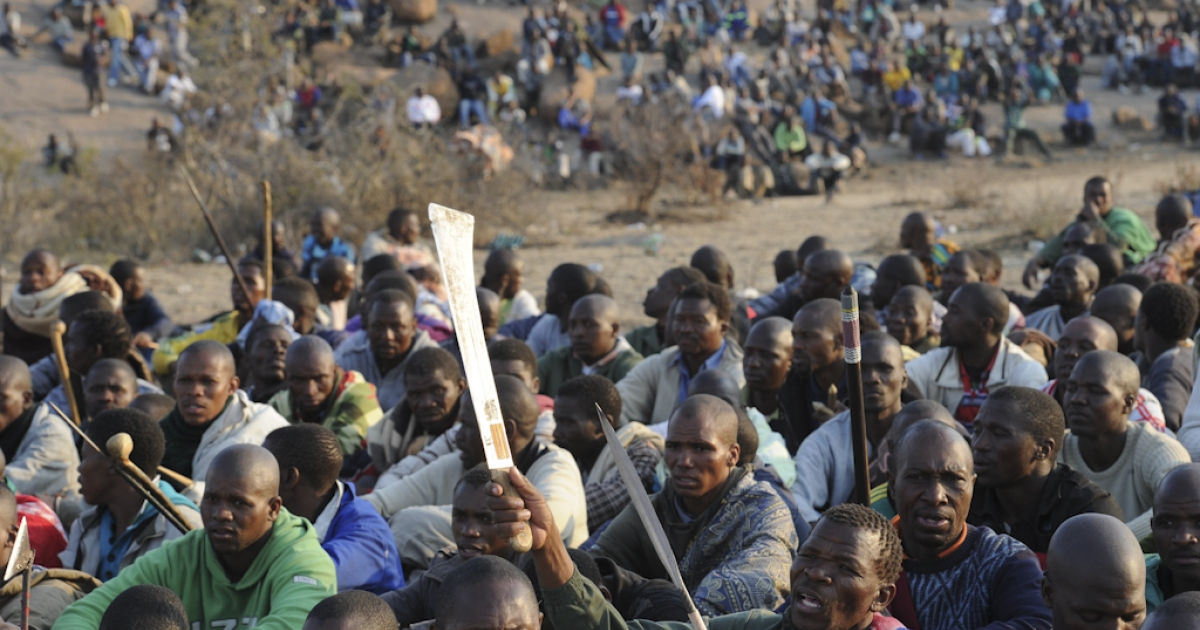 Striking mineworkers armed with machetes are monitered by a large number of police as they stage a sit-in on a hill near the Marikana mine in Rustenburg, 62 miles northwest of Johannesburg on August 15, 2012, where they are demading a wage increase. Ten people were killed in clashes at the platinum mine, which is run by leading producer Lonmin, between rival unions, the leading and decades-old National Union of Mineworkers (NUM) and the smaller Association of Mineworkers and Construction Union (AMCU).</p>
