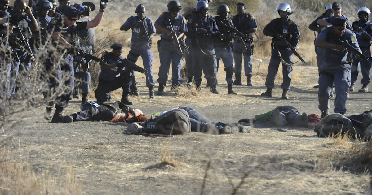 Police surround fallen miners after they opened fire during clashes at the Lonmin Marikana platinum mine near Rustenburg, South Africa, on August 16, 2012. Hundreds of workers armed with machetes, sticks and metal rods had gathered on a hillside near the mine, defying police orders to disperse. Several people were lying on the ground, some bleeding from wounds, after the crowd fled, according to an AFP reporter. Police say at least 30 people were killed.</p>