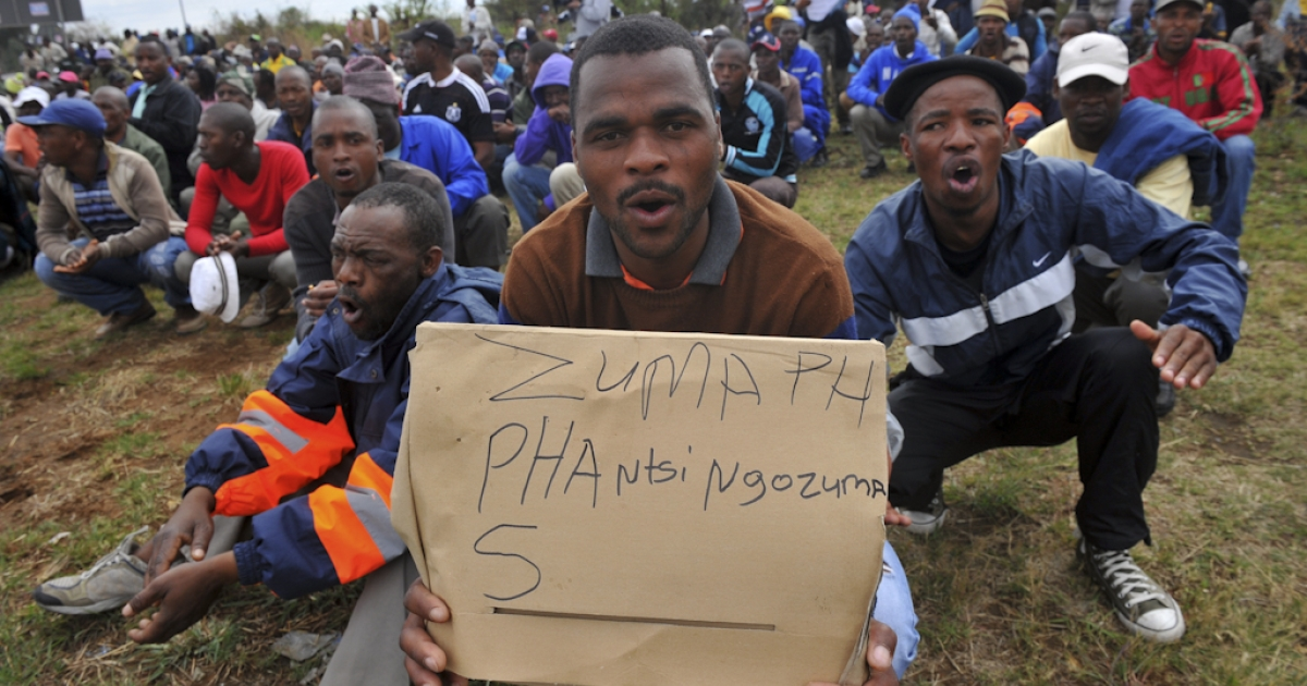 Demonstrators hold a placard during march by protesting miners in Rustenburg on September 16, 2012 after a security crackdown in the restive platinum belt where officers shot dead 34 strikers exactly a month ago.  Workers dispersed calmly after armoured trucks and armed police in riot gear stopped them from marching on a police station in northwestern Rustenburg, a day after officers fired rubber bullets on in nearby strike-hit Marikana.</p>