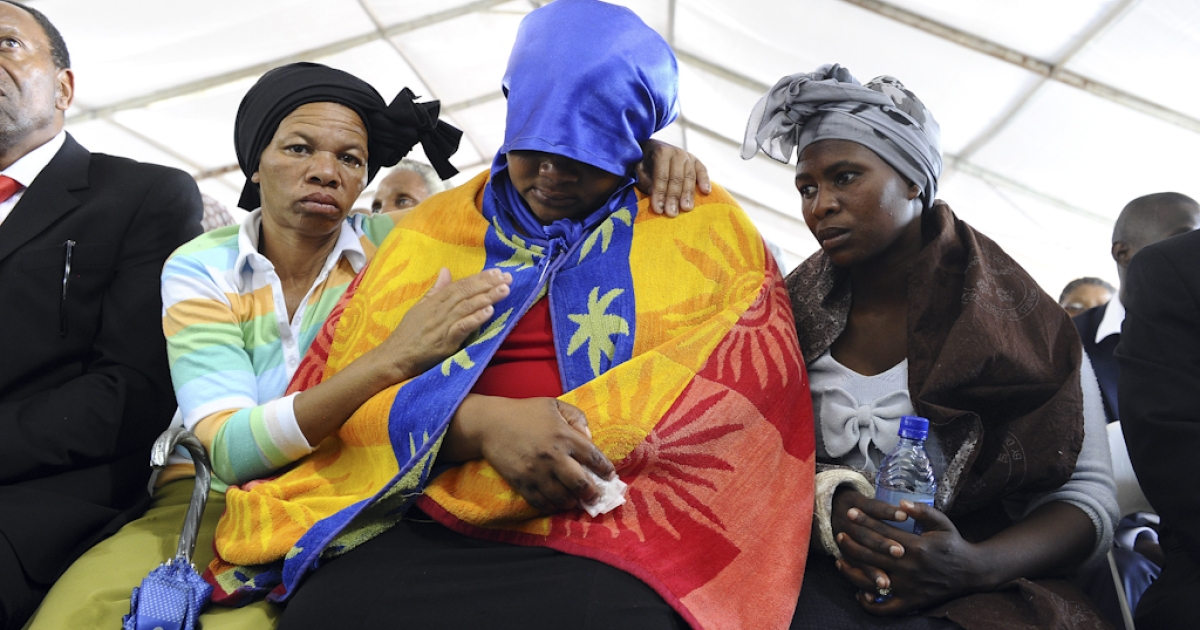 A woman is comforted during a memorial service for the 44 people killed in a wildcat strike at Lonmin's Marikana mine on August 23, 2012 in Marikana. Lonmin and nearby Impala Platinum closed for the day as workers prepared for memorials, including the main national service at Marikana where police gunned down 34 miners a week ago after deadly clashes had already claimed 10 people. The service at Lonmin will be the focal point during a day of mourning that will stretch across the country, as many of the victims were migrant workers whose bodies have already returned to their home villages.</p>